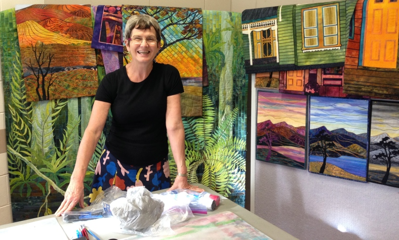 Gloria Loughman in front of her quilts