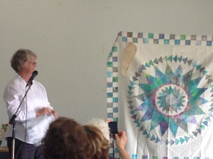 Lessa at a talk showing her Not a mariners compass 2 Sew Textiles